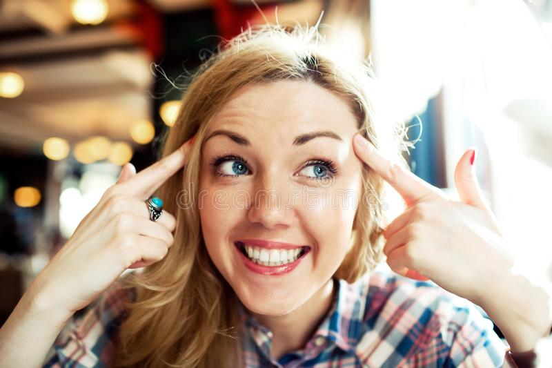 Das junge intelligente erfolgreiche weibliche Lächeln mit ihren Händen nähern sich Kopf lizenzfreie stockfotos