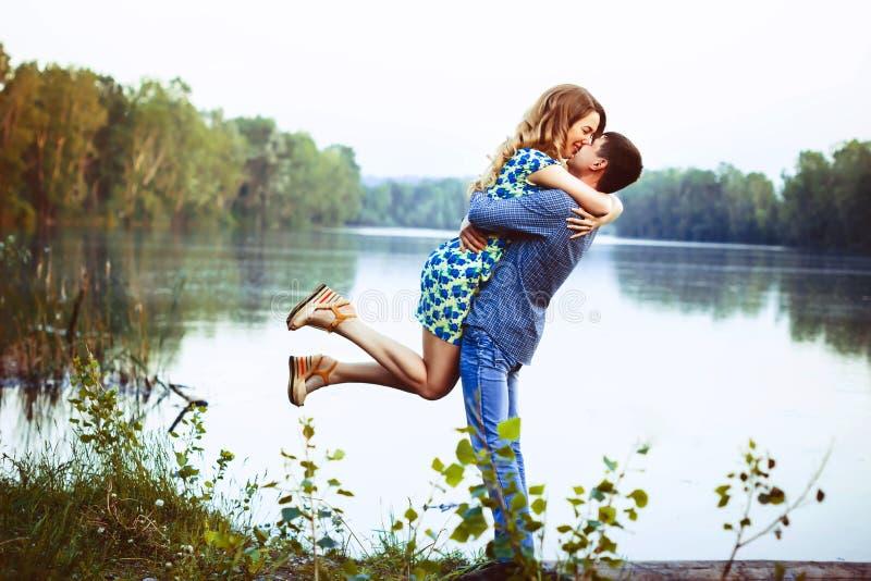 Das junge küssende Paar und freut sich am See lizenzfreie stockfotografie