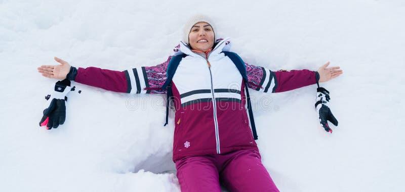 Das junge lächelnde weibliche Liying auf dem weißen Schnee öffnete weit ihre Arme stockfotografie