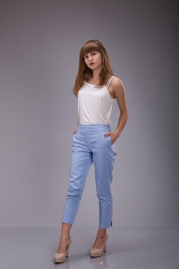 Das junge langhaarige Mädchen in einem weißen Hemd auf einem grauen Hintergrund stockfotos