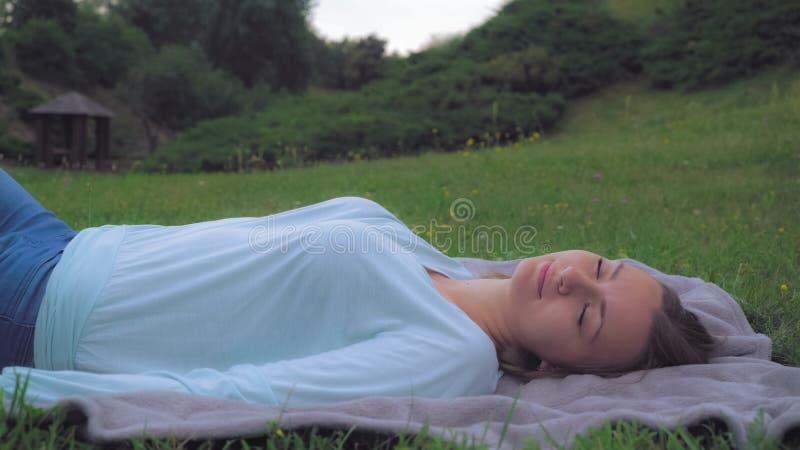 Das junge Mädchen, das auf dem Rasen im Park, eine Mitteilung an Ihrem Telefon gewinnend liegt, schließt dann seine Augen und das stockfotos