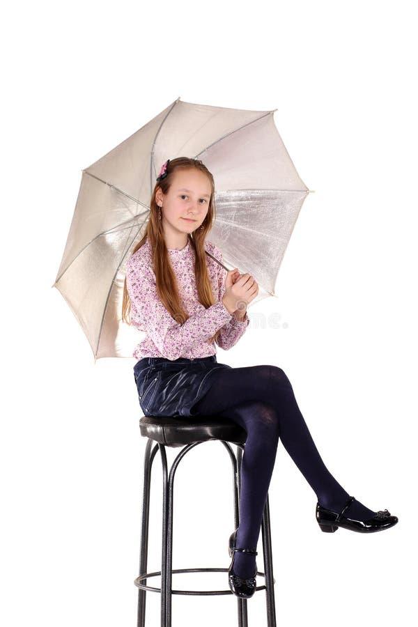 Das junge Mädchen auf einem Stuhl mit einem Regenschirm lizenzfreie stockfotos