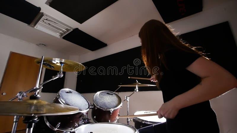 Das junge Mädchen, das auf einer Trommel trainiert, stellte in ein Musikstudio ein Ansicht von der Unterseite lizenzfreie stockbilder