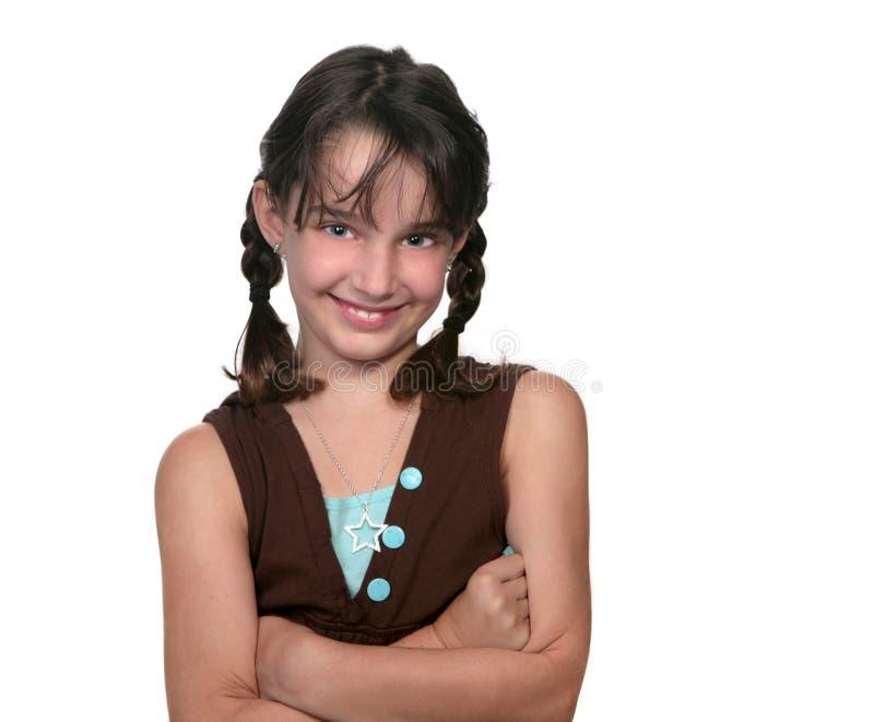 Das junge Mädchen, das mit ihren Armen lächelt, faltete sich lizenzfreies stockfoto