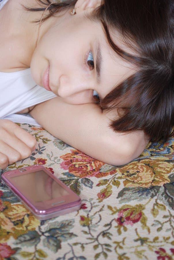 Das junge Mädchen der Jugendliche liegt auf einem Bett und betrachtet durchdacht das Telefon, das nahe ihm liegt stockbild