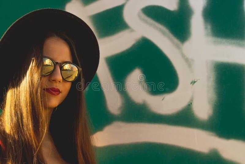 Das junge Mädchen des Hippies, das moderne Sonnenbrille und schwarzen Hut mit Graffiti als Hintergrund trägt stockbilder