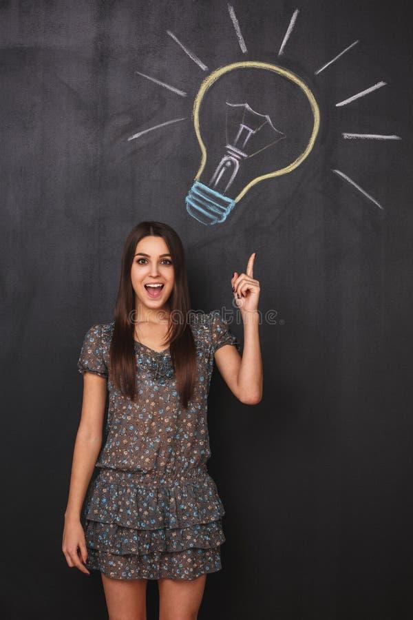 Das junge Mädchen hat eine gute Idee und hebt ihren Finger oben zeigend auf eine Glühlampe auf dem Brett an lizenzfreies stockfoto