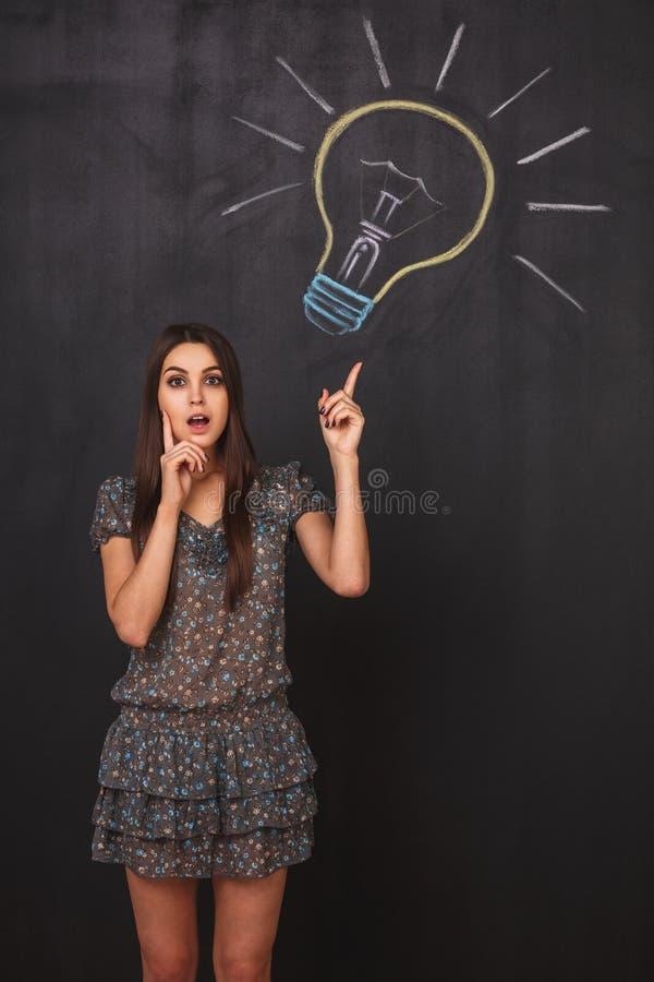 Das junge Mädchen hat eine gute Idee und hebt ihren Finger oben zeigend auf eine Glühlampe auf dem Brett an stockfoto