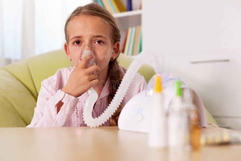 Das junge Mädchen, das Inhalatorgerät verwendet - entlasten Sie Asthma und Allergien s stockfotografie