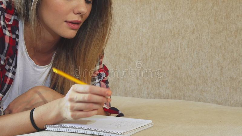 Das junge Mädchen schreibt in ihr Notizbuch lizenzfreie stockfotografie