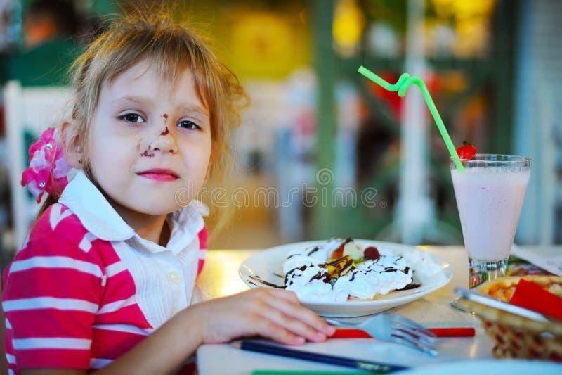 Das junge Mädchen sitzt in einem Café und wird Eiscreme essen und ein milchiges Cocktail trinken lizenzfreies stockfoto