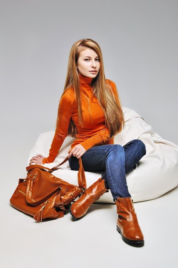 Das junge Modemädchen, das in der modischen Kleidung in den Lederstiefeln mit Tasche sitzt lizenzfreies stockbild