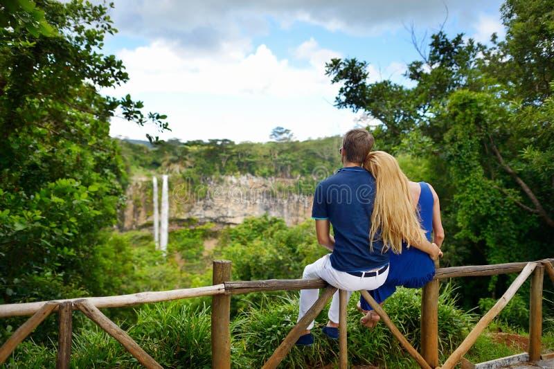 Das junge Paar, das eine Ansicht über Chamarel genießt, fällt stockfotos