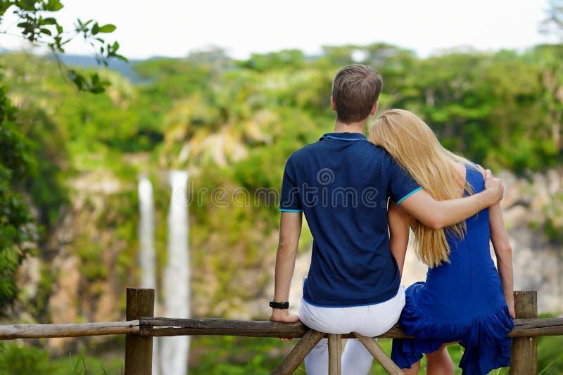 Das junge Paar, das eine Ansicht über Chamarel genießt, fällt stockbild