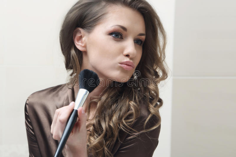 Das junge schöne Mädchen tut Make-up stockbild