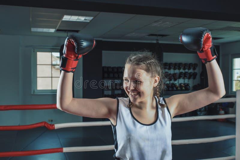 Das junge sch?ne M?dchen im Sportring hob oben ihre H?nde den Sieg feiernd und gl?cklich l?chelnd an stockfotografie