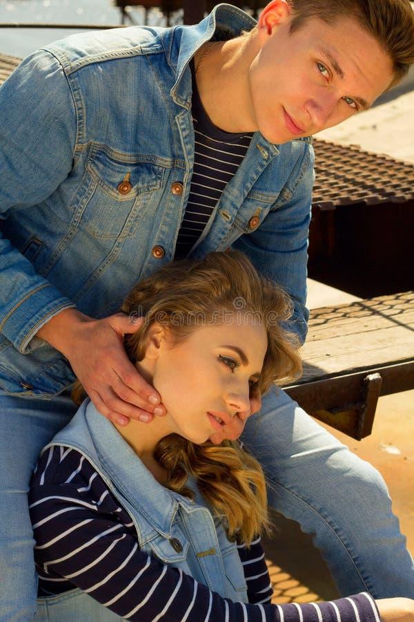 Das junge schöne Modepaar, das Jeans trägt, kleidet im Tageslicht stockfotografie