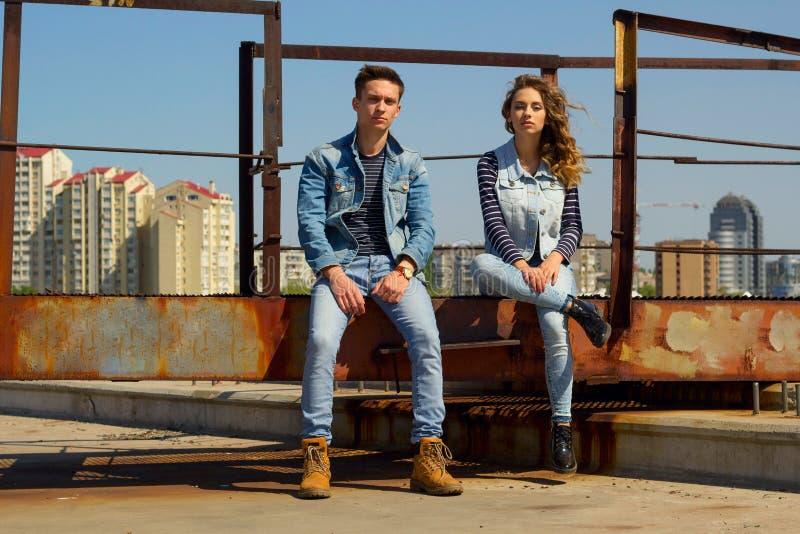Das junge schöne Modepaar, das Jeans trägt, kleidet im Tageslicht stockbild