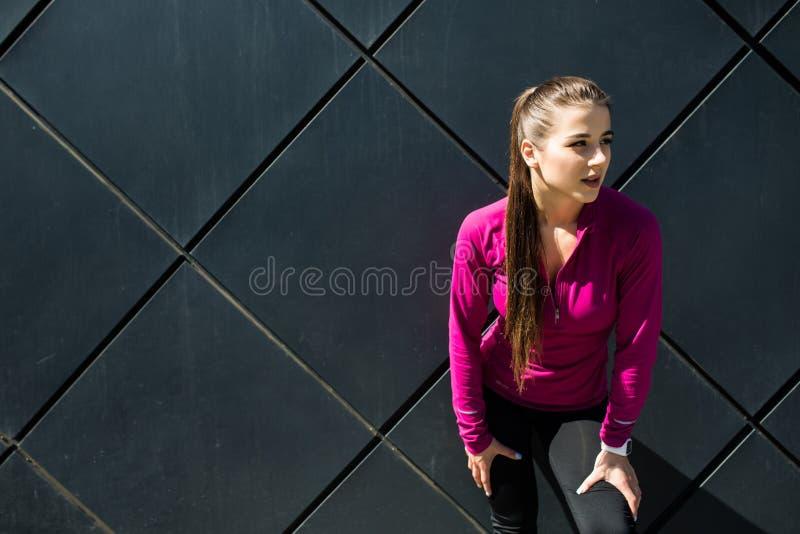 Das junge sportliche Mädchen, das rosa Sportkleidung trägt, entspannen sich nach ausarbeitendem, Training im Freien, Gefühlsfreih lizenzfreies stockbild