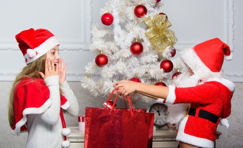 Das Jungenkind, das als Sankt mit weißem künstlichem Bart gekleidet werden und der rote Hut geben dem Mädchen Geschenkbox Sankt h lizenzfreie stockfotos