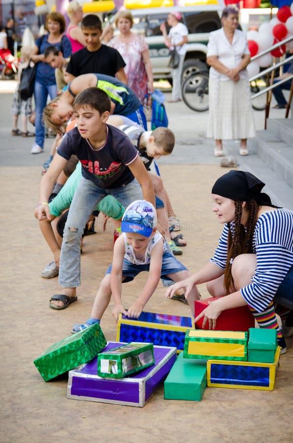Das Jungenteam, das Spaßspiel spielt, führen sich Kasten zwischen ihre Beine an der Piratenpartei lizenzfreies stockfoto