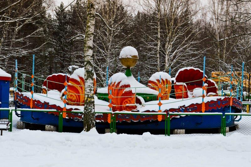 Das Karussell der leere schneebedeckte kalte Kinder, Anziehungskraft im Park im Winter lizenzfreies stockfoto