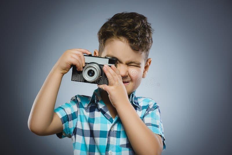 Das Kind, das ein Foto unter Verwendung einer Retro- Entfernungsmesserkamera macht, lokalisierte grauen Hintergrund lizenzfreie stockfotos