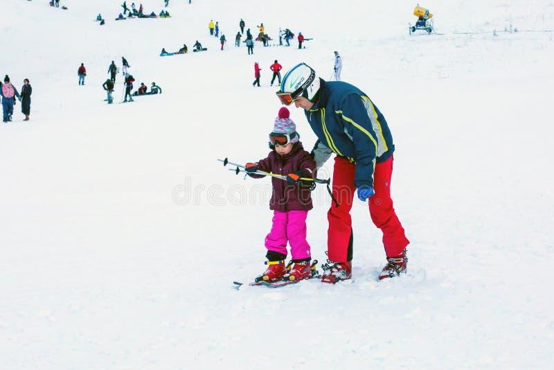 Das Kind, das lernt, auf der Steigung herein Ski zu fahren und zu bemannen stockfotografie