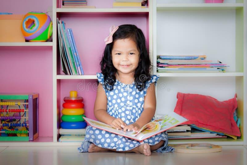 Das Kind, das, nettes kleines Mädchen gelesen wird, ist lächelnd lesend und ein Buch lizenzfreies stockbild