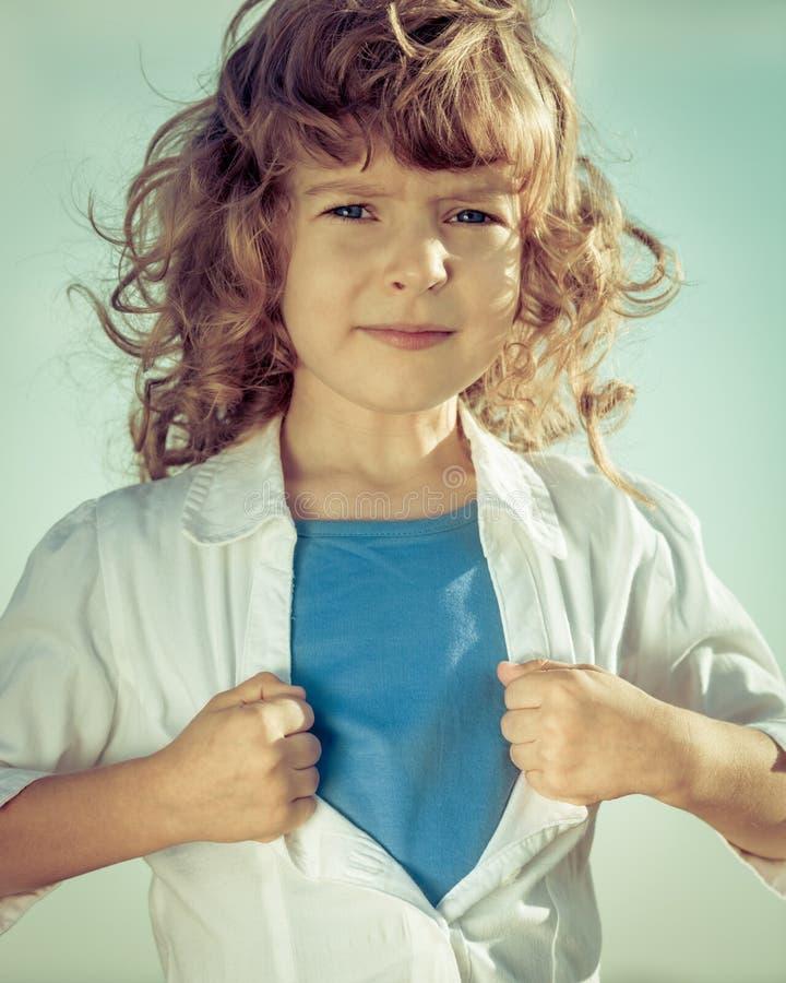Das Kind, das sein Hemd öffnet, mögen einen Superhelden lizenzfreie stockfotos