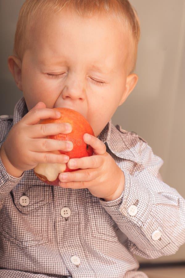 Das Kind des kleinen Jungen Kinder, dasapfel isst, tragen zu Hause Früchte lizenzfreie stockbilder
