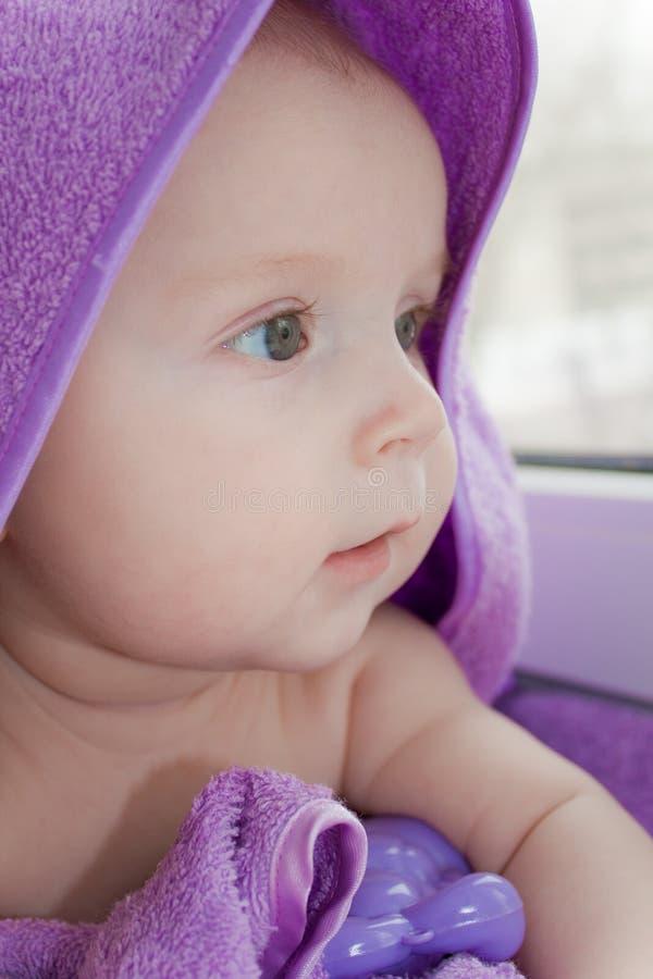 Das Kind in einem lila Tuch schaut den überraschten Anblick stockbild