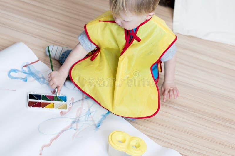 Das Kind in einer gelben Weste zeichnet eine Bürste auf einem Weißbuchesprit lizenzfreies stockfoto