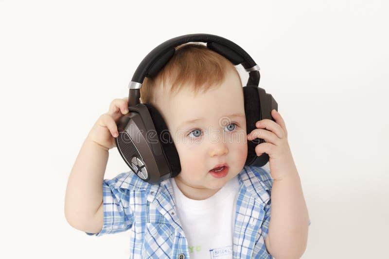 Das Kind hört Musik in den großen Kopfhörern lizenzfreie stockfotografie