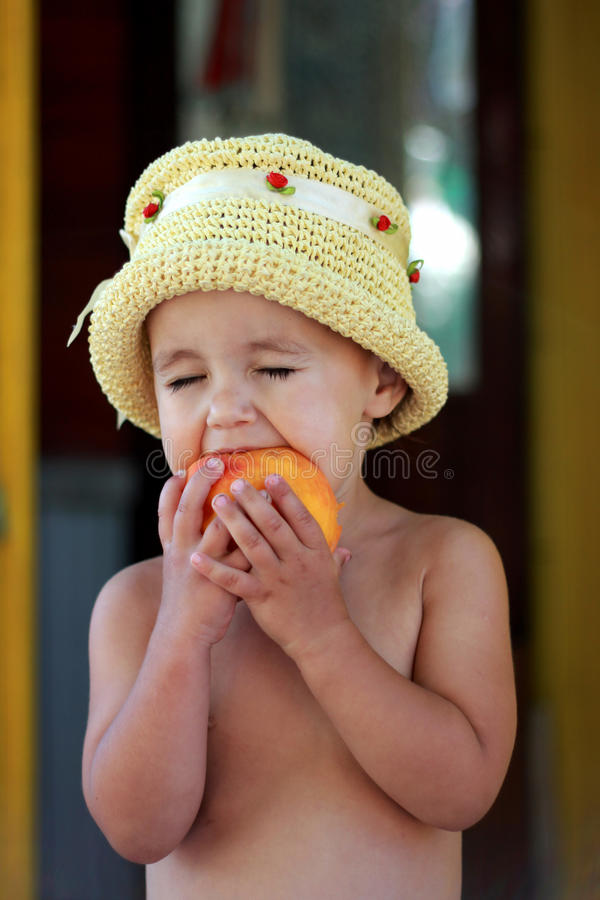 Das Kind isst einen geschmackvollen Pfirsich stockbilder