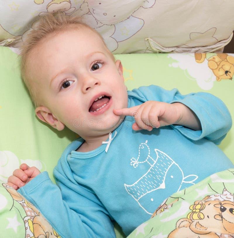 Das Kind liegt in einem Bett und holte einen Finger zu einem Mund stockfotografie