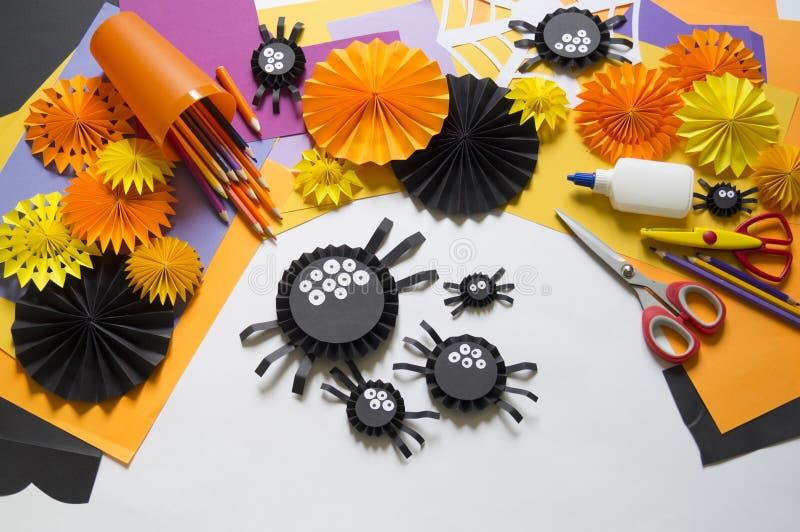 Das Kind macht schwarze Spinnen vom Papier Vorlagenklasse Handgemachte Fertigkeiten stockbilder