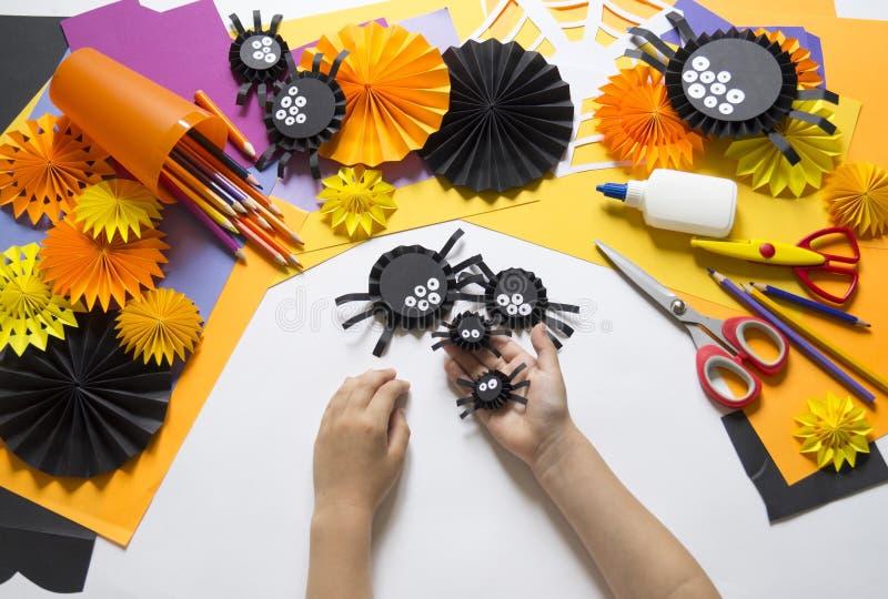Das Kind macht schwarze Spinnen vom Papier Vorlagenklasse Handgemachte Fertigkeiten stockfotos