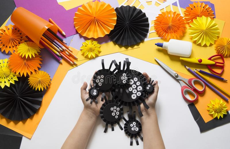 Das Kind macht schwarze Spinnen vom Papier Vorlagenklasse Handgemachte Fertigkeiten lizenzfreies stockfoto