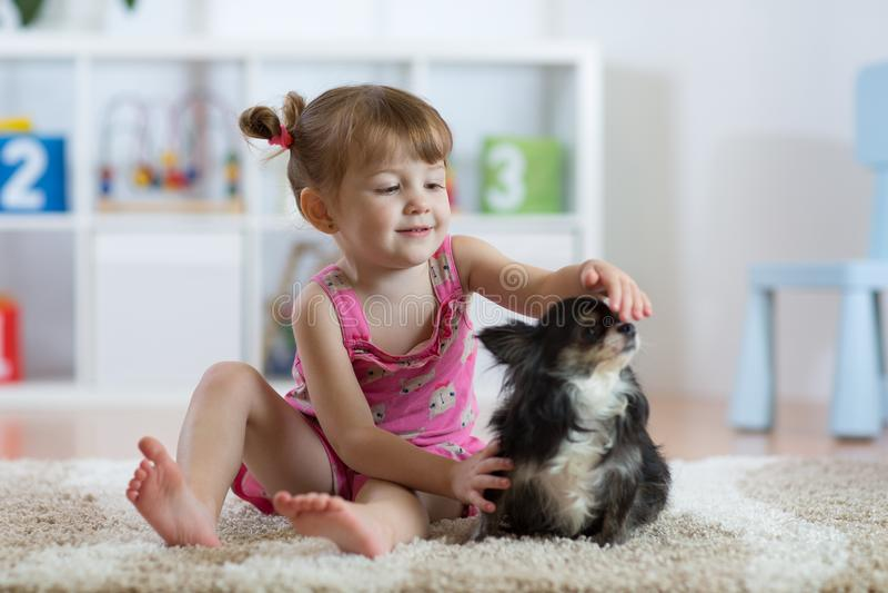 Das Kind mit dem Hund, der zu Hause auf Boden sitzt stockfotografie