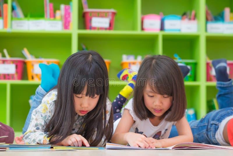Das Kind mit zwei Mädchen legen auf Boden- und Lesegeschichtenbuch im prescho nieder lizenzfreie stockfotografie