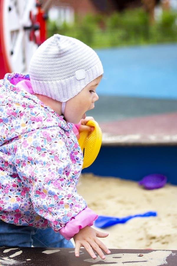 Das Kind schreit beim Sitzen im Sandkasten Das Baby in der Kappe öffnete seinen Mund Baby geht in das Yard auf stockbilder