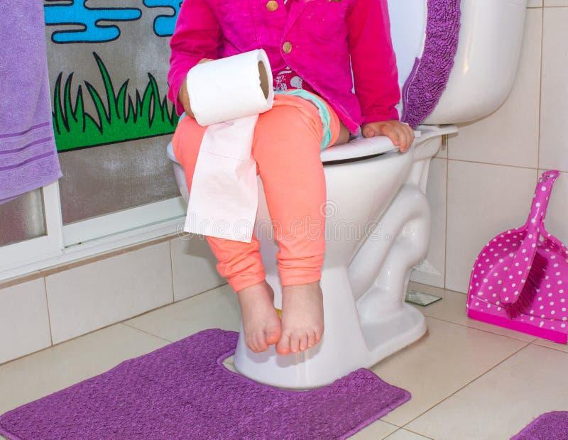 Das Kind sitzt in der Toilette und hält in den Händen des Toilettenpapiers lizenzfreies stockfoto