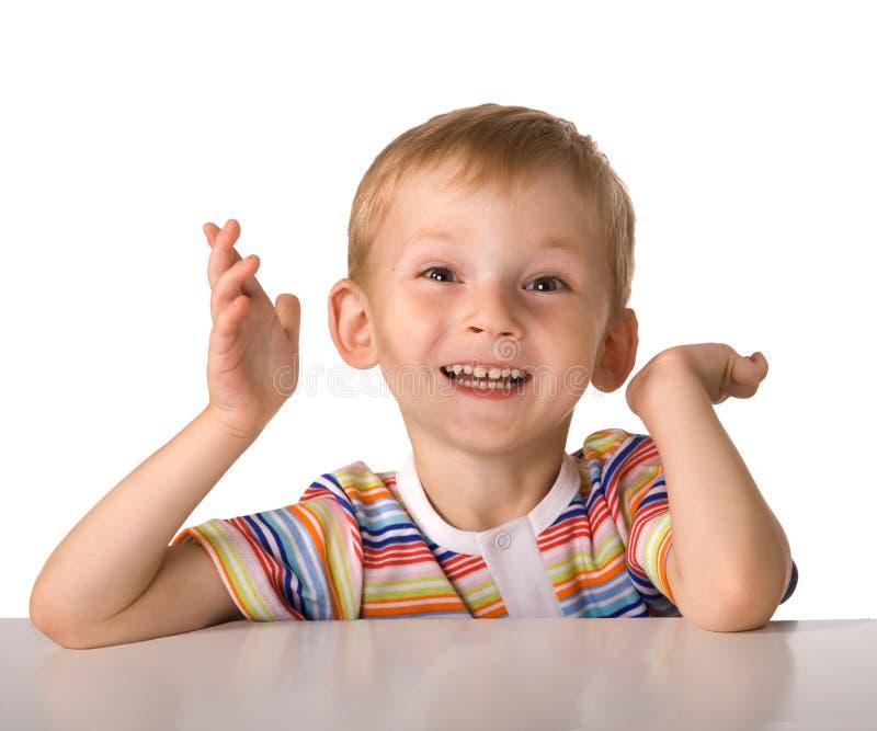 Das Kind sitzt an einem Tisch lizenzfreies stockbild