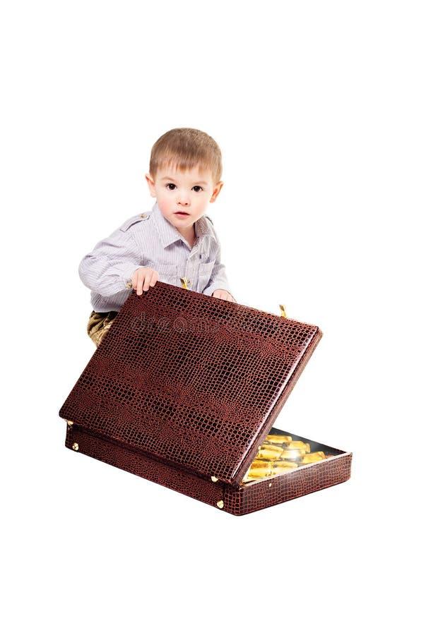 Das Kind sitzt mit einem Koffer, der von den Goldbarren voll ist stockfotografie