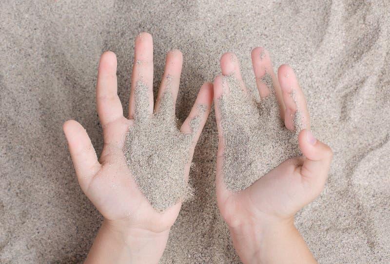Das Kind spielt mit dem Meersand Sypet, weg fliegend Entspannen Sie sich, Meditation stockbild