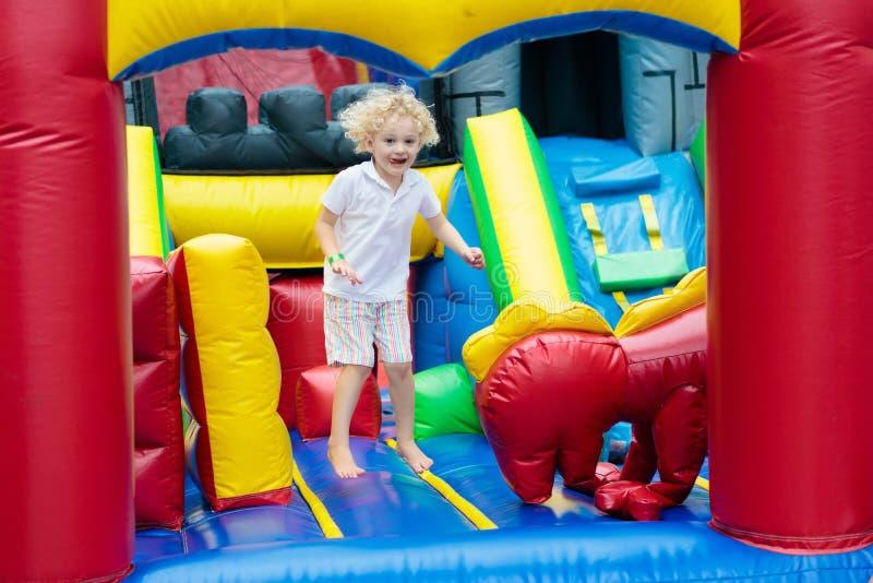 Das Kind springend auf Spielplatztrampoline Kinder springen lizenzfreie stockfotografie