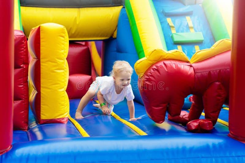 Das Kind springend auf Spielplatztrampoline Kinder springen stockbild