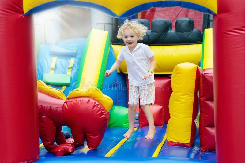 Das Kind springend auf Spielplatztrampoline Kinder springen stockfoto