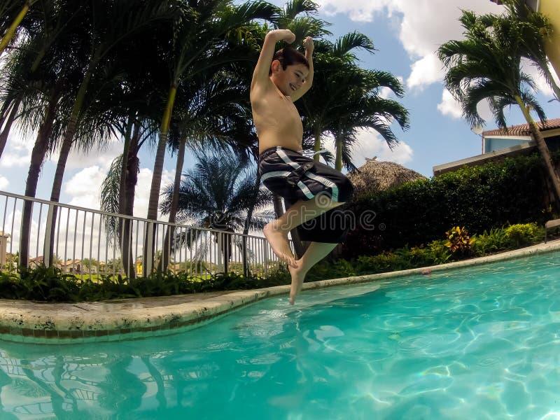 Das Kind springend in Pool stockfotos